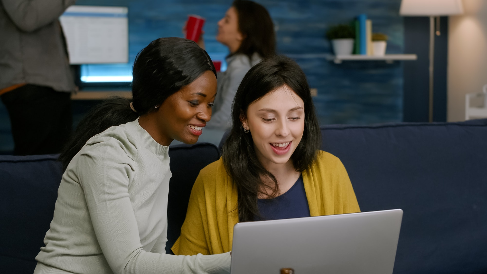 Multiracial friends laughing while watching funny video on laptop